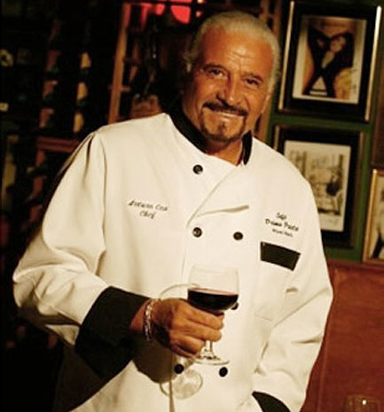 Chef Arturo Cea with his white uniform and a cup of wine in the right hand